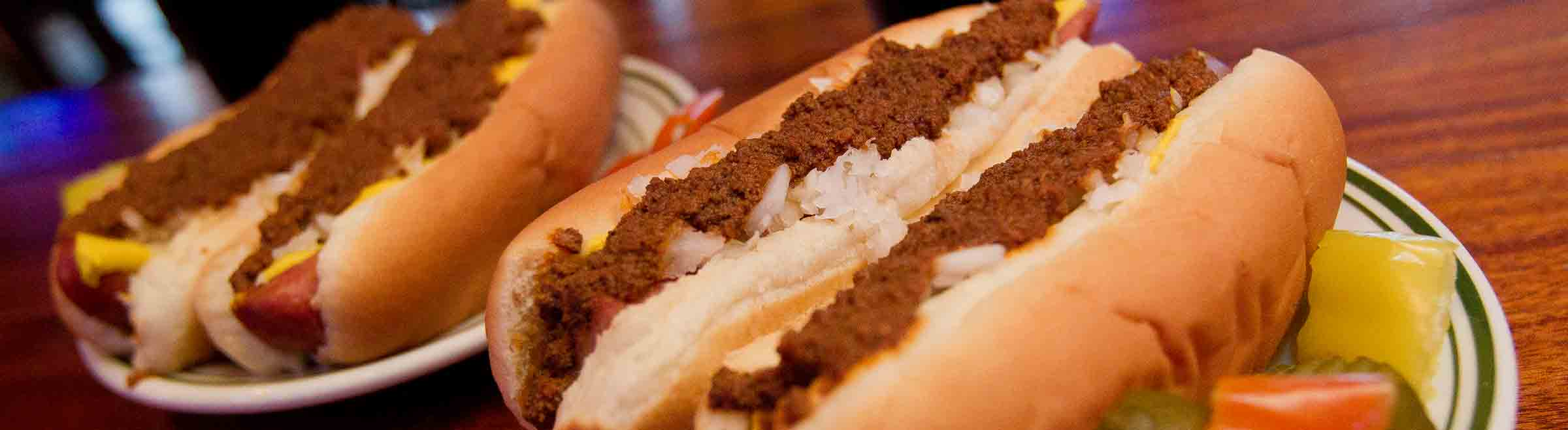 Close up of four Tony Packos Famous Hungarian Hot Dogs topped with Chili on plates