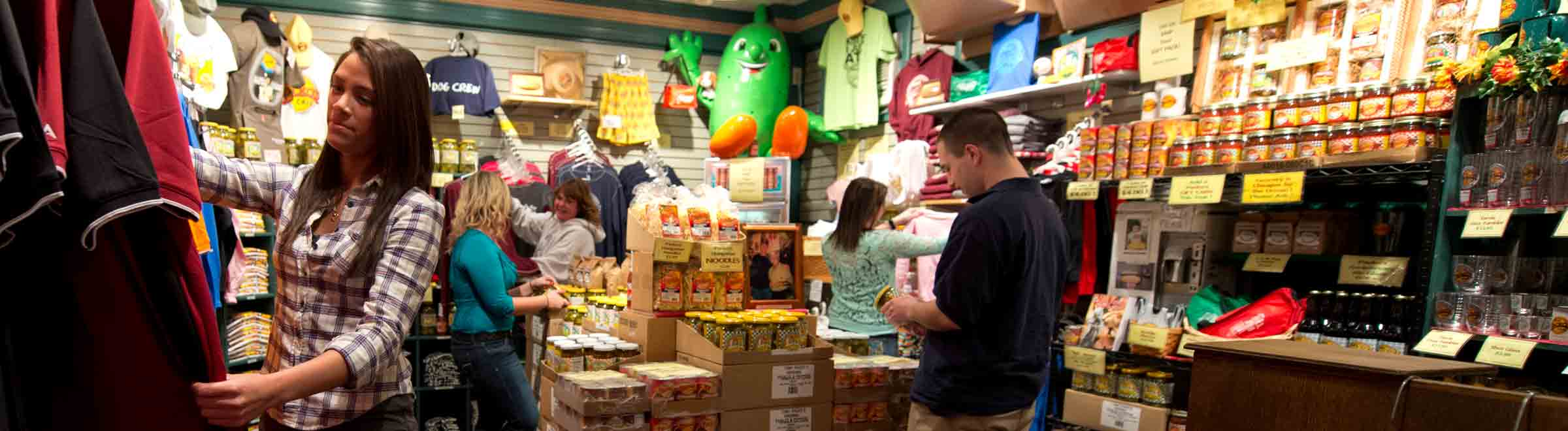 Five people browsing Tony Packo's physical gift shop; looking at tshirts, pickles, peppers and other Packo merchandise