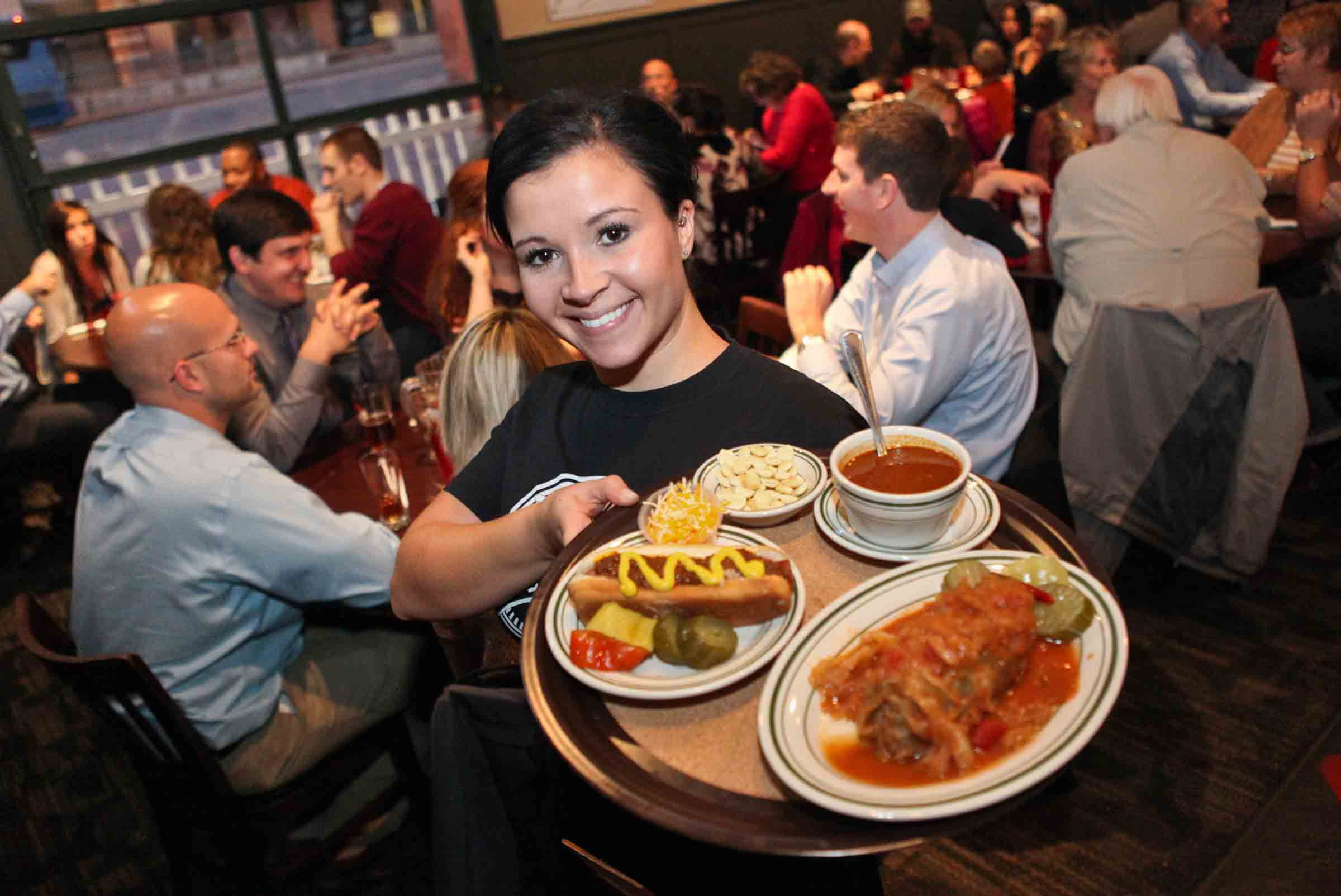 Waitress Serving Tony Packos to Hungry Customers enjoying themselves in the restaurant